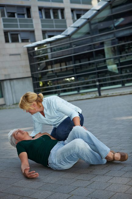 Passerby helping a senior woman with seizure